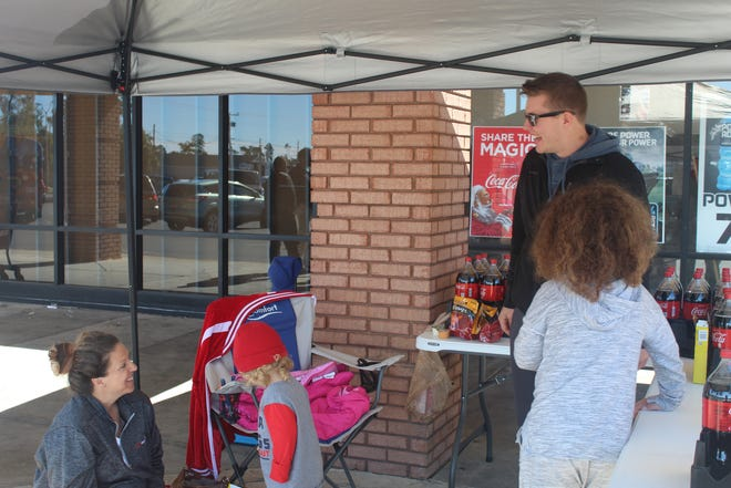 Volunteers pass out free 2-liter Coca-Colas for toy donations for Stuff The Bus.
