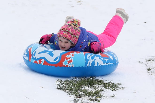 Sarah Burchett, 4, of Delaware grips the handles of her snow tube as she sleds down a hill at the Delaware park.