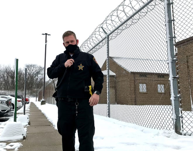 Zach Rushin, a Delaware County corrections officer, listens to his radio outside the facility at 844 U.S. Route 42 N. in Delaware. The county has approved the $97,980 purchase of a new closed-circuit TV system for the jail. Cameras will be installed at spots that include the tall pole behind Rushin and will monitor all areas, including the fenced-in section on the right.