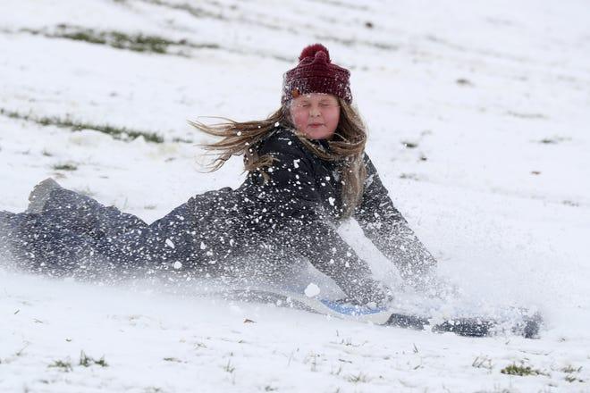 Madelyn Sutton, 8, of Delaware turns her head to avoid the flying snow as she sleds down a hill at Gallant Woods Park in Delaware on Dec. 1 after central Ohio's first measurable snowfall.