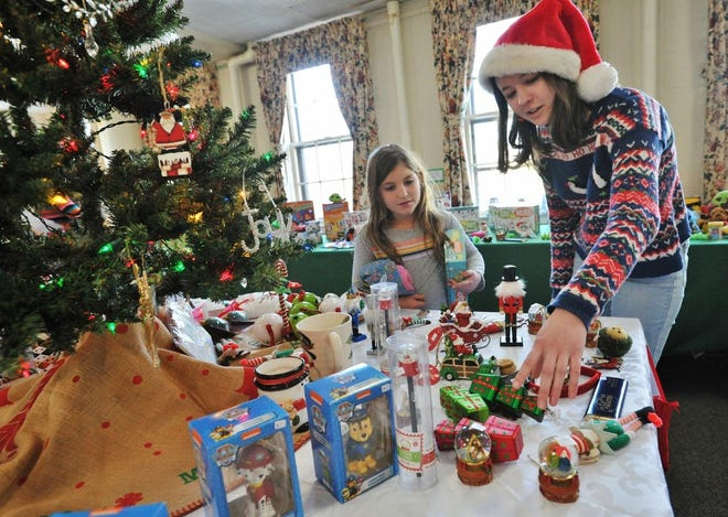 "Caroline McCallion, 9, of Cohasset, left, is helped by ""Elf"" Katharyn Hassan of Cohasset in selecting holiday gifts in the Appalachia Service Project's ""Secret Shopping Room"" at St. Stephen's Episcopal Church during the Cohasset Village Holiday Fair on Dec. 7, 2019."