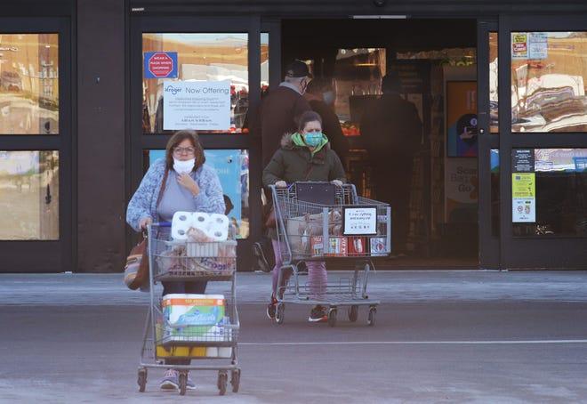 Shoppers exit the front entrance of Kroger Marketplace on Dec. 2, 2020, in Royal Oak.