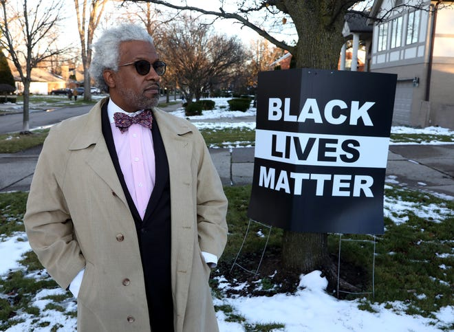 Attorney Todd Russell Perkins stands in front of a large Black Lives Matter sign at his home in Grosse Pointe Shores on Wednesday, Dec. 2, 2020. Perkins has had the sign up since October and is fighting the $500 ticket that the city of Grosse Pointe Shores issued him because they say it violates a city ordinance on large political signs. Perkins says the sign is not political and he's not in violation because of it.
