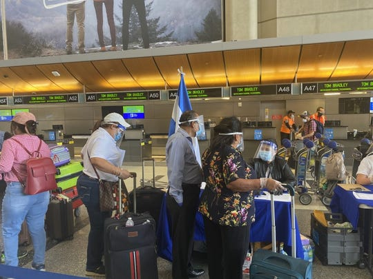 A group of El Salvador residents fly out of Los Angeles International Airport on June 30.