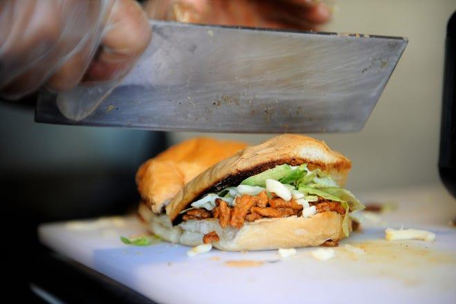 Carlos Rivera cuts the finished torta in half to serve at La Plaza food truck on Saturday, Nov. 28, 2020.