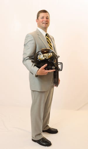 Southern Miss head football coach Will Hall poses with a Golden Eagle football helmet.