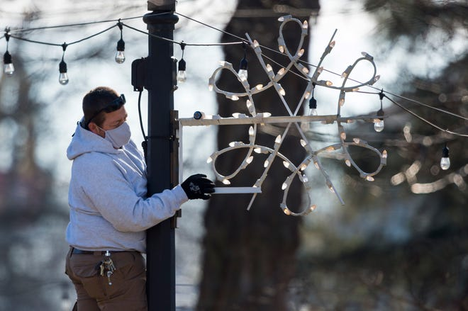 "Facilities worker Bruce Sigler hangs a snowflake in Central Park Tuesday morning, Dec. 2, 2020, as Henderson decorates for its annual ""Christmas in the Park"" display."