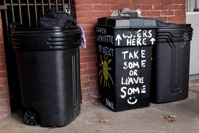Bins filled with cold weather apparel sit on a Main Street porch for those who are in need, Tuesday, Dec. 1, 2020 in Lafayette.