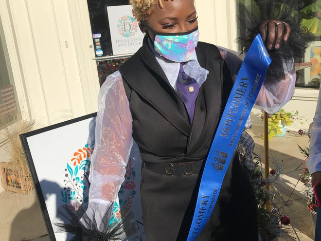 Owner Aretha Dix holds a ribbon during an opening event for her new Cloverdale business Divine Vines and Decor.