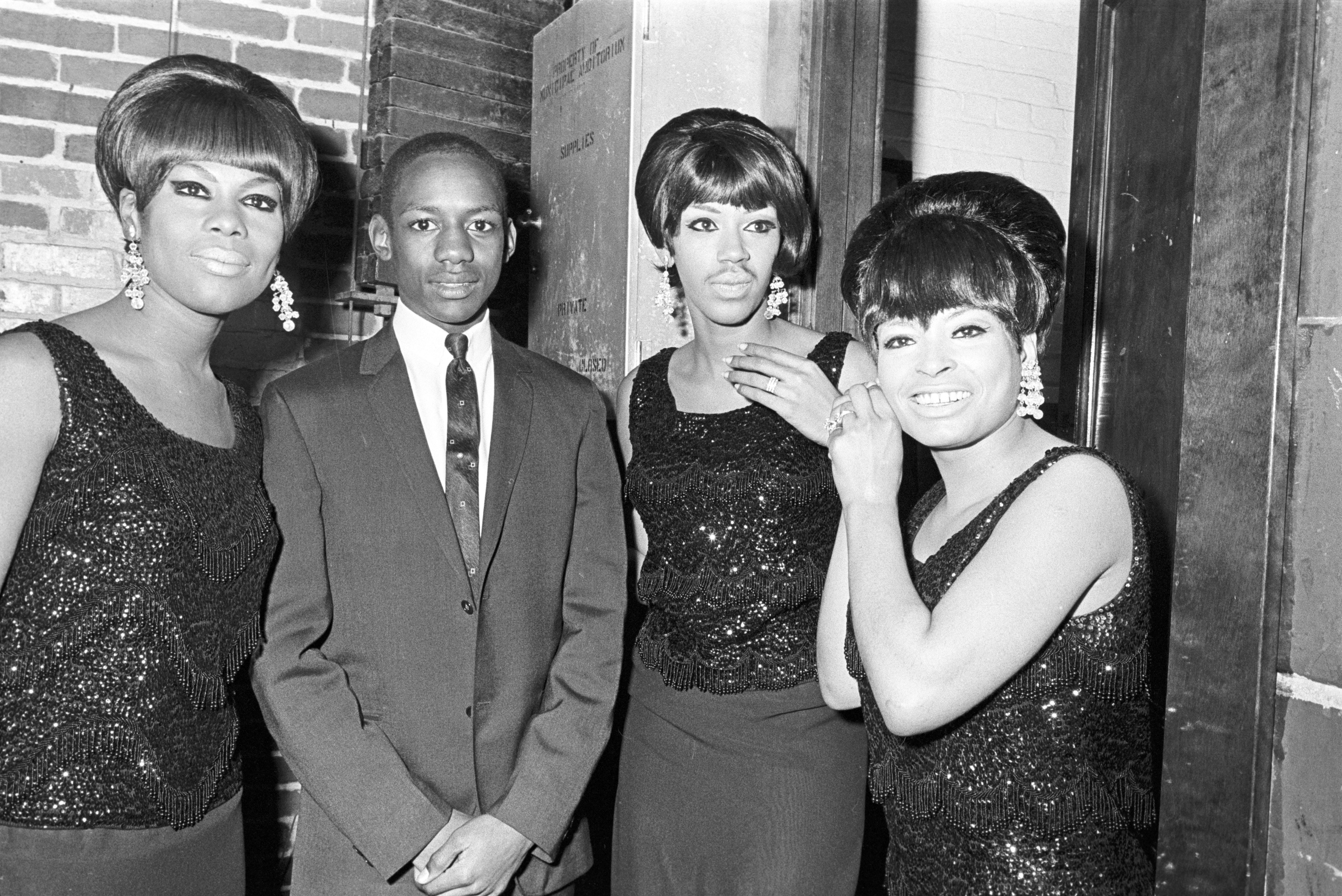 A young man stands with the Marvelettes at the Montgomery City Auditorium during a performance of the Otis Redding Show