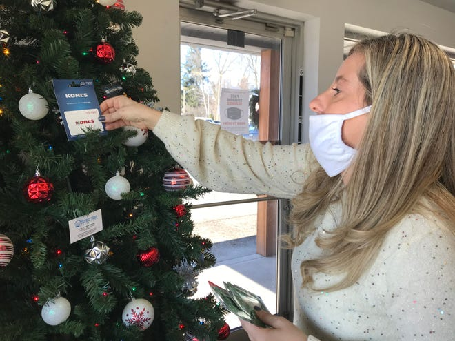 Amber Cramer, co-owner of Central Ohio Garage Door, places a donated gift card onto a Christmas tree in their facility. She and her husband, Brian Cramer, organized a community toy drive for families of students at Stevenson and Garfield Elementary Schools.