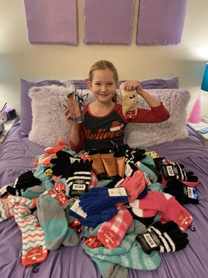 Atleigh Johnson, 9, puts together gift bags of fuzzy socks and foot cream for cancer patients at Memorial Medical Center.