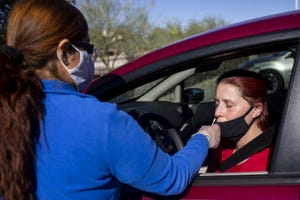 Judith Salcido, a medical assistant at Embry Women's Health, takes a nasal swab sample from Melissa Nelson at a COVID-19 testing site on Dec. 2, 2020, in Peoria, Ariz.
