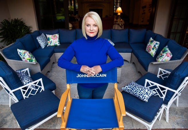 Cindy McCain stands behind a director's chair with her late husband's name.