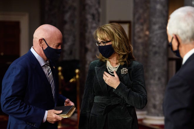 Former NASA astronaut and Democratic U.S. Sen. Mark Kelly of Arizona (left) speaks with his wife, former U.S. Rep. Gabrielle Giffords of Arizona, after being sworn in by then-Vice President Mike Pence (right) during a ceremonial event at the U.S. Capitol in Washington, D.C., on Dec. 2, 2020.