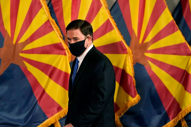 Arizona Republican Gov. Doug Ducey arrives for a news conference to talk about the latest Arizona COVID-19 information on Dec. 2, 2020, in Phoenix.