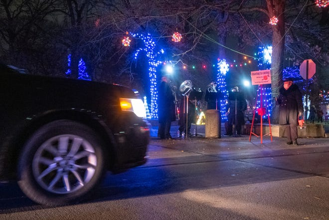 A Salvation Army bell-ringer collects donations during  Sperry's Santa Drive-thru Spectacle Friday, Nov. 27, 2020, in Pine Grove Park. This year's Santa parade was held in a drive-thru format due to the COVID-19 pandemic.