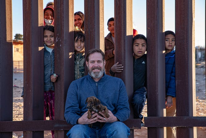 Former El Paso Times photojournalist Mark Lambie stops at a stretch of border wall where some Mexican children come to greet him whenever he visits. They are shown Tuesday, Dec. 1, 2020. It was Lambie's last day at the El Paso Times.
