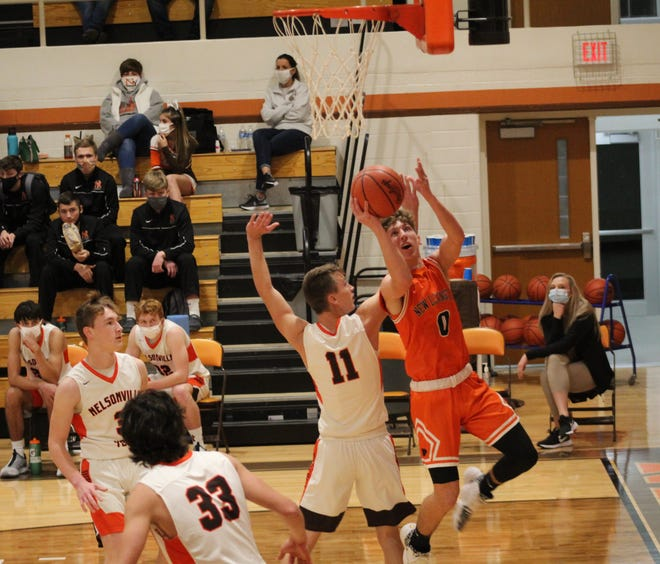 New Lexington's Brady Hanson (0) drives against Nelsonville-York's Ethan Gail (11) during Tuesday's non-league game inside Ben Wagner Gymnasium