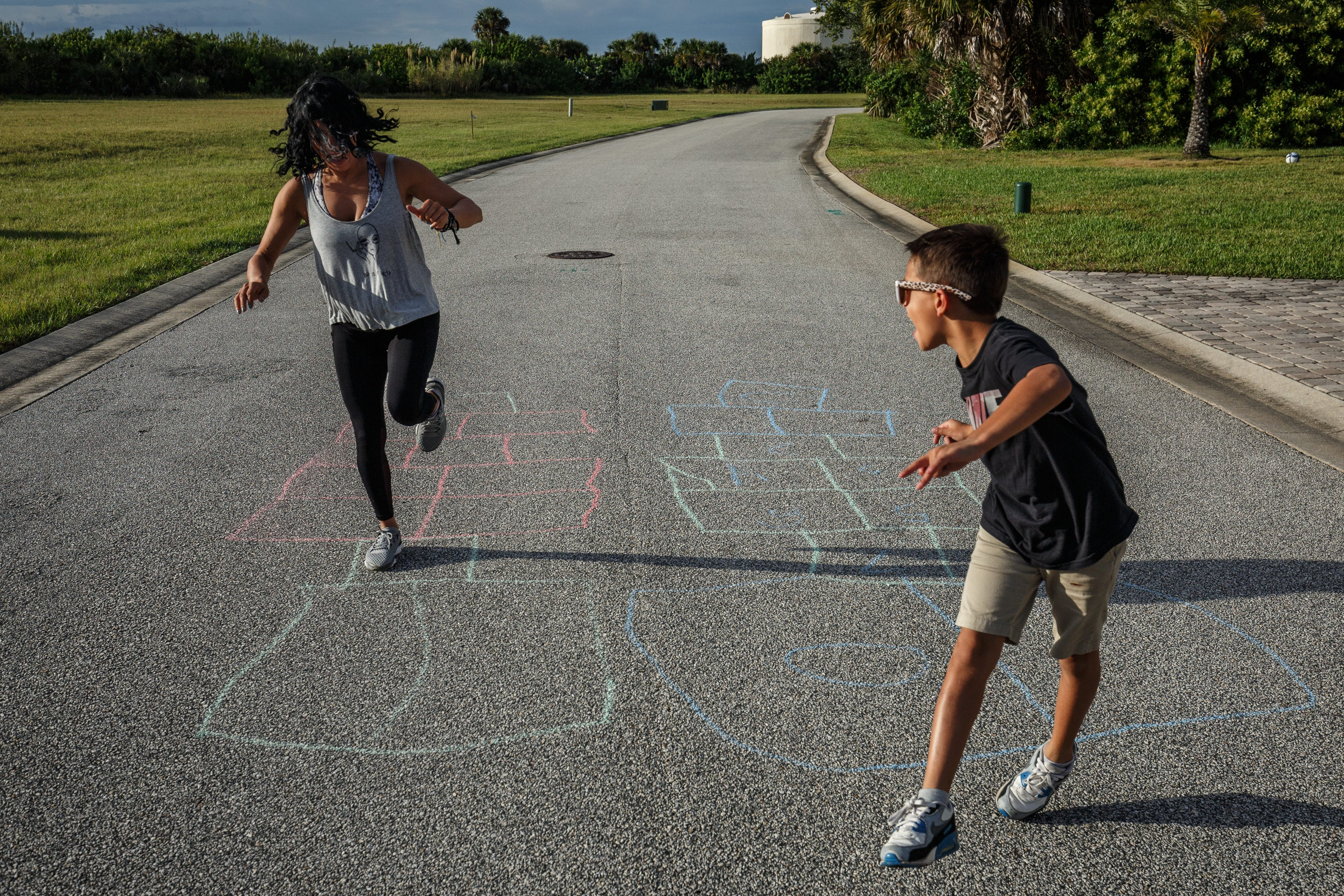 Lena and her son, William, play hopscotch.