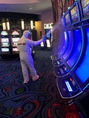 A worker for Belfor Property Restoration in Birmingham, Michigan, sprays disinfectant while 'deep cleaning' a casino to remove any trace of COVID-19.