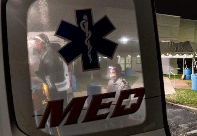 A stretcher is wiped down and loaded into an ambulance on Tuesday night after EMTs dropped off a patient at a newly opened field hospital operated by Care New England to handle a surge of COVID-19 patients in Cranston, R.I.