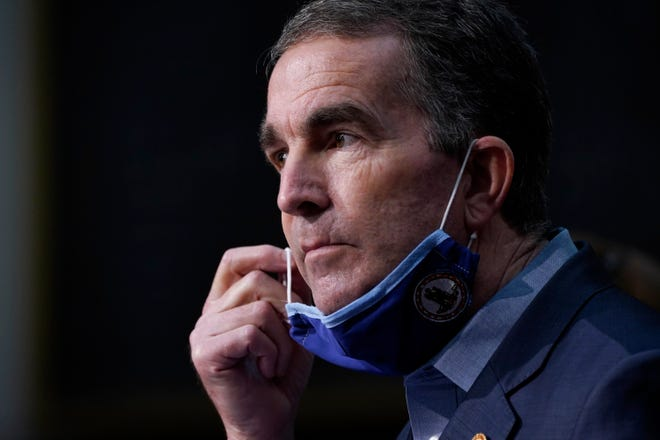 Virginia Gov. Ralph Northam removes his mask to answer a question during a COVID-19 briefing at the Capitol in Richmond, Va, Wednesday Nov 18, 2020.