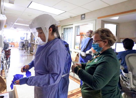 Deb Dalsing, nurse manager of the COVID-19 treatment unit at UW Health, assists nurse Ainsley Billesbach with her personal protective equipment Nov. 5  in Madison, Wis.