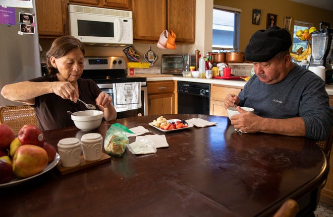 Maria and Nelson Toala eat breakfast in their home, where they also care for two of their granddaughters who are 8 and 10. The Toalas moved from Ecuador to the United States in 2006. Nelson Toala had been the provider for his family and was working as a cook at the Driskill Hotel until he was furloughed because of the pandemic and then had a stroke.