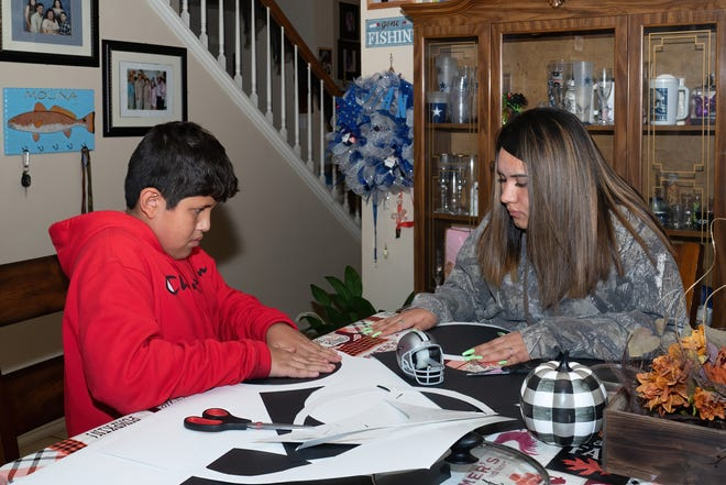 Jordan, 12, and Jennifer, 15, Molina work together to make Halloween decorations in their Pflugerville home. The kids have dealt with the death of their father in August in different ways.