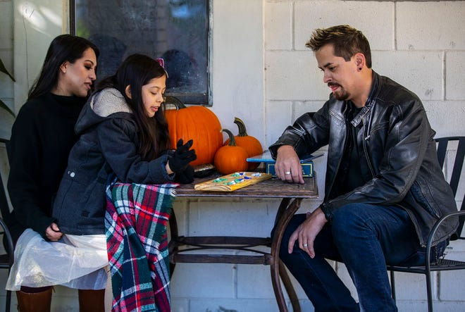 Aaron Kemkaran, 36, daughter Kirstan, 8, and wife, Mayra Reyes, 32, play a board game outside their Georgetown home, where they live with her parents. Before the coronavirus pandemic he was making a living as a musician and music studio owner.