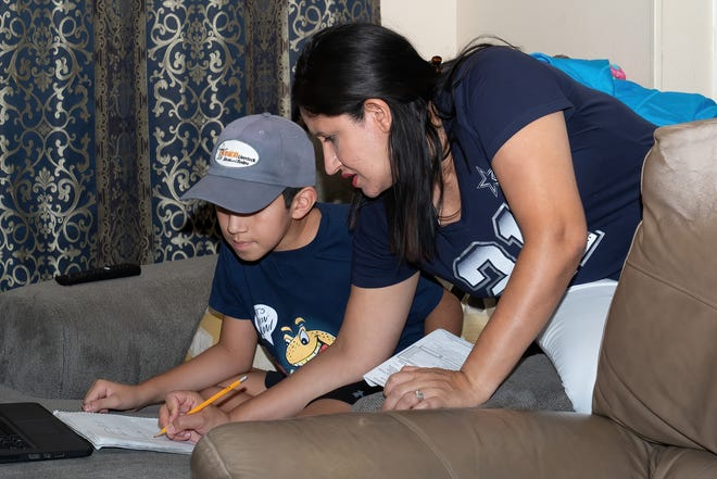 Jessica Molina, 39, helps her son Juan, 10, with his math homework in their Pflugerville home. When school started this year, she was helping all four kids get onto their classes while teaching her own preschool class and caring for her husband, Juan, who died a few days after school started of kidney cancer.