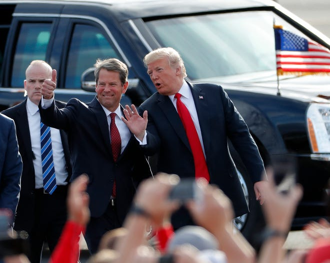 In this Nov. 4, 2018, file photo, then-Georgia Republican gubernatorial candidate Brian Kemp, left, walks with President Donald Trump as Trump arrives for a rally in Macon, Ga. (AP Photo/John Bazemore, File)