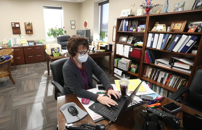 Summit County Health Commissioner Donna Skoda answers emails from school superintendents in her office Thursday as the county prepares to hit the purple tier on Ohio's coronavirus advisory map.  [Mike Cardew/Beacon Journal]