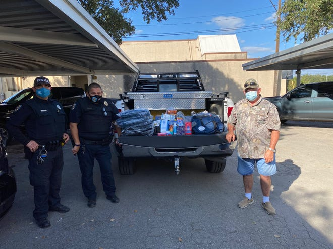 Officer  Homero Mendoza , Lt. Enrique Saenz and Michael Cooke from the South Texas Gun and Bow Club donating items to give to the homeless.