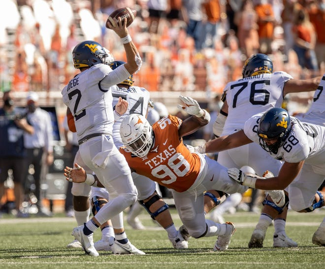Texas defensive lineman Moro Ojomo, shown pressuring West Virginia quarterback Jarret Doege during last season's game, will be counted upon to replace the pass-rushing shoes left by Joseph Ossai. There were nine credited sacks during Saturday's Orange-White game.
