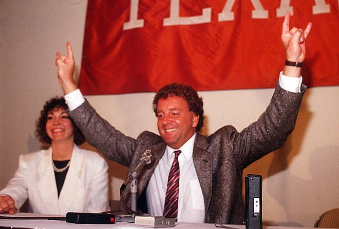 Tom Penders gives the hook em horns sign after being annouced as the new University of Texas basketball coach April 6, 1988. [Larry Kolvoord/American-Statesman, File]