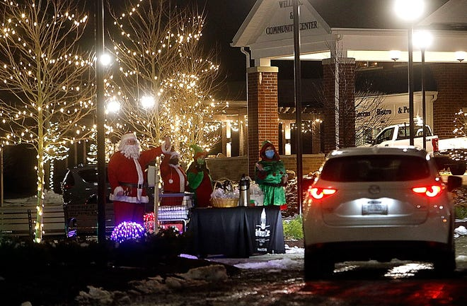 Santa greets a car at the Light It Up with Brethren Care Village's drive thru campus light display was held Wednesday, Dec. 2, 2020. Santa was on hand with his elves handing out cookies and candy canes to visitors. TOM E. PUSKAR/TIMES-GAZETTE.COM