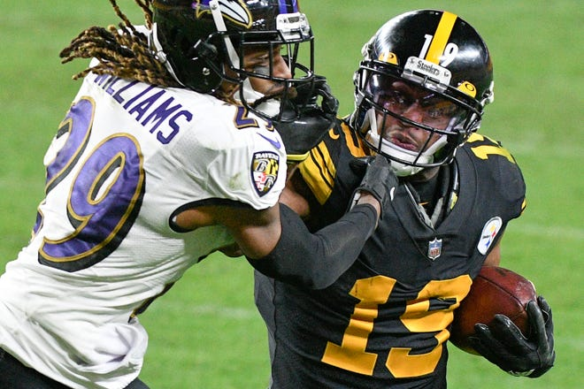 Pittsburgh Steelers wide receiver JuJu Smith-Schuster (19) tries to fend off Baltimore Ravens cornerback Tramon Williams after making a catch during the second half of an NFL football game Wednesday in Pittsburgh.