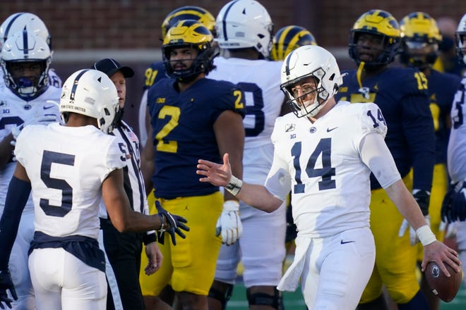 Penn State quarterback Sean Clifford (14) celebrates his team's win over Michigan with wide receiver Jahan Dotson (5) on Saturday in Ann Arbor, Mich.
