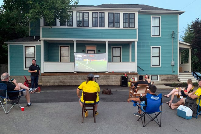 A small group of Columbus Crew fans has gathered in the Budd Dairy Food Hall parking lot to watch Crew games for most of this season. They project the game onto a screen on the porch of a house next door, which happens to be the home of a Crew fan, and this is how they plan to watch Sunday's Eastern Conference Final game against the New England Revolution.
