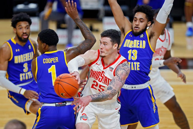 Ohio State Buckeyes forward Kyle Young (25) passes the ball against Morehead State Eagles guard DeVon Cooper (1) and forward Jaden Stanley-Williams (13) during the first half of their game at Covelli Center in Columbus, Ohio on December 2, 2020.