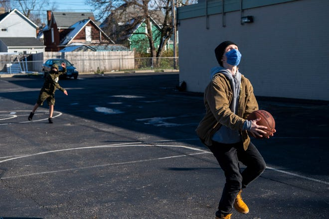 """Frank Smith, 16, right, takes a jump shot while Troy Ross, 13, tosses a football during their outdoor break from homework at the City Life Center in Franklinton on Dec. 2. City Life is  one of more than 100 sites throughout the city servingas a free """"learning extension center"""" for Columbus students during the COVID-19 pandemic."""