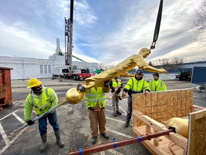 Crews carefully place the Angel Moroni statue, removed by crane from atop the Latter-day Saints' Columbus Ohio Temple, into a large wooden box on Thursday. As part of the temple's renovation, the spire on which the eastward-facing statue sits is being rebuilt before the 150-pound gold-leafed character from the Book of Mormon is returned.