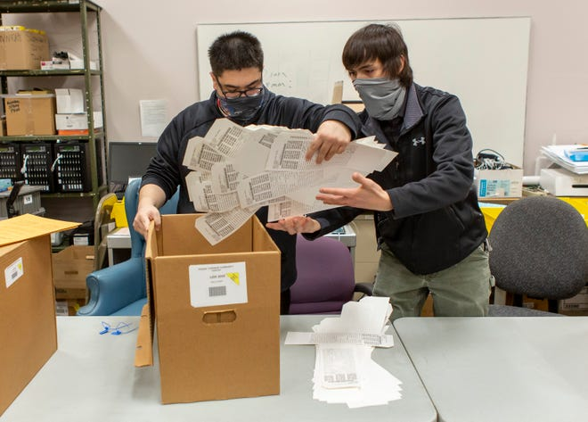 Tony Nguyen, left, and Aaron To organize voting machine results from a Prairie Township precinct as they perform a recount of election-day ballots from Ohio Senate District 16 at the Franklin County Board of Elections headquarters in Columbus on Dec. 3.