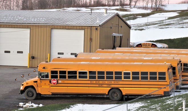Part of the West Holmes bus fleet sits idle at the transportation center at West Holmes High School while students are learning remotely.