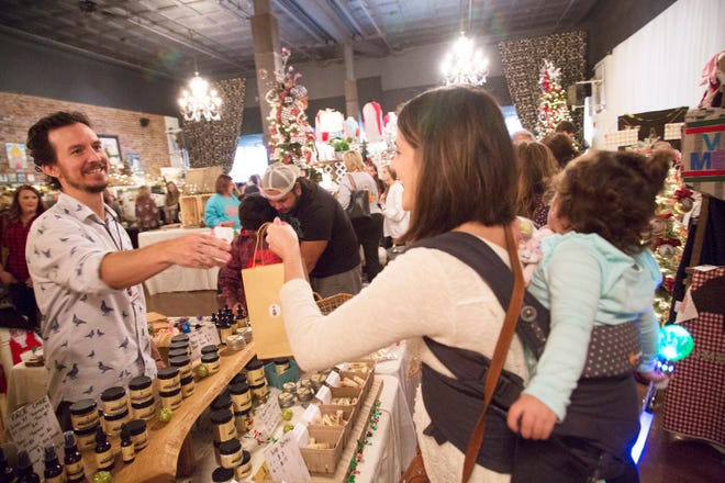 Michael Rehker of Queen Bee Farm hands a bagged glass of his local honey to Paloma Rodriguez and her daughter Evy during  at Very Maury Christmas Holiday Market held in the Westbury House in downtown Columbia on Saturday, Nov. 18, 2017.