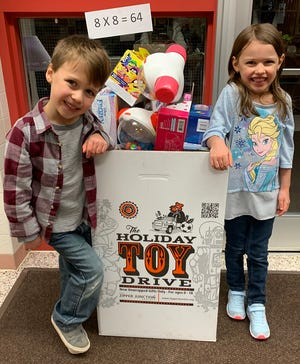 Generating momentum. Aubrey and Dakota Granville pose with a donation box into which all sorts of toys were placed for Christmas last year.