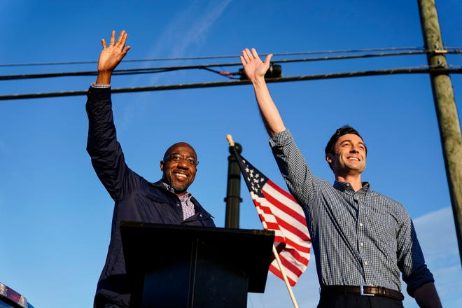 Georgia Democratic candidates for U.S. Senate Raphael Warnock, left, and Jon Ossoff gesture toward a crowd during a campaign rally in Marietta, Georgia.
