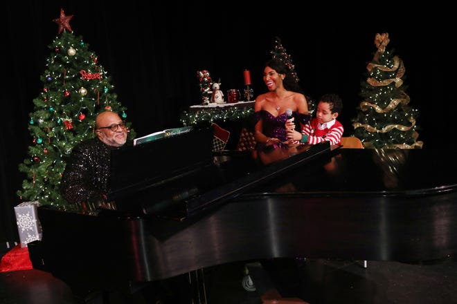 """Musician BK Davis, along with his daughter, Nyilah Davis, and her son, Mason Gabel, 7, rehearse a song Monday, Nov. 30 at the Capitol Theater in Burlington. The performance was recorded by Lori Wilson for a holiday music concert and will be shown on the Capitol Theater's movie screen. """"Coming Together A Christmas Celebration of our Community"""" will be shown at 2 and 7 p.m. Saturday and several other times throughout the month."""